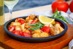 Frying-pan with slices of fish, tomatoes, onions and lemon. On wooden board on the table Stock Image