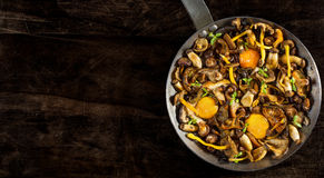 Frying pan steel with mushrooms and soft egg yolks. Stock Image