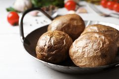Frying pan with tasty baked jacket potatoes on table, closeup. Frying pan with tasty baked jacket potatoes on wooden table, closeup stock photography
