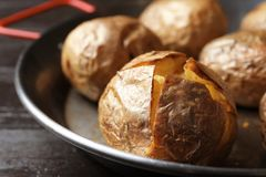 Frying pan with tasty baked jacket potatoes on table, closeup. Frying pan with tasty baked jacket potatoes on wooden table, closeup stock image