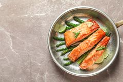 Frying pan with tasty cooked salmon on table. Top view Stock Image