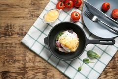 Frying pan with tasty egg Benedict. On table stock photo