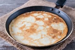 Frying pan with tasty thin pancakes on wooden table stock images