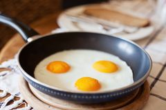 Frying pan with three fried eggs Stock Photography