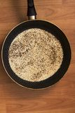 Frying pan with toasted sesame seeds top view stock photography