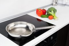 Frying pan and vegetables in modern kitchen Stock Photography