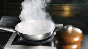 Frying pan with White thick steam in restaurant kitchen. Cooking duck meat. Slow motion. White Water Vapour. Food video.  stock video