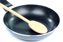 Frying pan and wooden spoon. Stock Photo