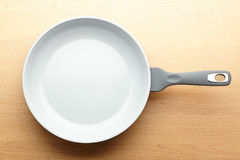 Frying pan on wooden table background. Top view Royalty Free Stock Image