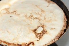 Frying pancake in the frying pan Royalty Free Stock Photo