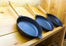 Frying pans on wooden shelf closeup Royalty Free Stock Photography