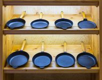 Frying pans on wooden shelf, cooking tools Stock Images