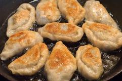 Frying polish homemade fried dumplings known as pierogi. stock photos