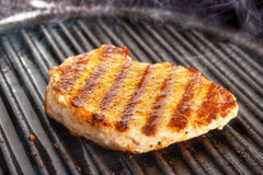 Frying pork fillet. Cooked pork fillet on cast iron grill pan Royalty Free Stock Images