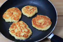 Frying potato pancakes. Potato pancakes cooking in a frying pan Royalty Free Stock Photography