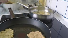 Frying potato pancakes on pan and oil stock footage