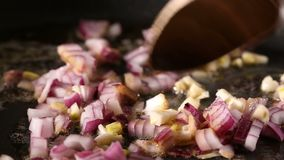 Frying purple onion and garlic with butter in pan stock footage