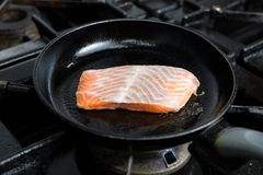 Frying salmon in pan Royalty Free Stock Images