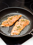 Frying salmon. Frying raw salmon in a pan Stock Photos