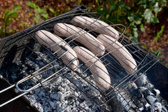 Frying of sausages on a brazier Stock Photos
