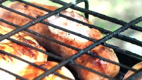Frying sausages on the grill around the campfire. Close-up video. Macro. stock video footage
