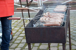 Frying of sausages on a street brazier. Food Stock Photography