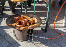 Frying sausages and tasty pieces of lard on an outdoor barbecue propane disc cooker Royalty Free Stock Photos