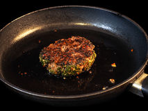 Frying seasoned hamburger in fry pan Stock Images
