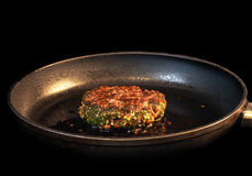 Frying seasoned hamburger in fry pan Royalty Free Stock Images