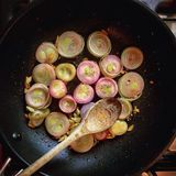 Frying shallots. Shallots and garlic cooking in a pan Royalty Free Stock Photos