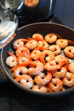 Frying shrimp. Photo of shrimp being fried in butter on a black frying pan. Shallow depth of field with focus across the middle Stock Photos