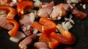Frying smoked bacon with onion and red bell pepper on frying stock video