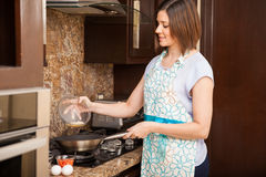 Frying some eggs in the kitchen Stock Images