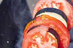 Frying tomatoes and eggplant. Frying red tomatoes and dark eggplant on a fire while relaxing in the forest. photo close-up, small depth of field, selective focus Stock Photography