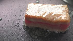 Frying and turning over tuna fillet in oil on non stick frying pan. Clip stock video footage