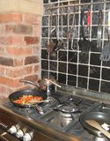 Frying up a meal in a rustic kitchen. Royalty Free Stock Image