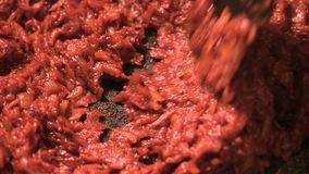 Frying vegetables with tomato paste. Chopped onions and carrots fried in vegetable oil with tomato paste in the pan. Close-up on top of a kitchen tile stock video