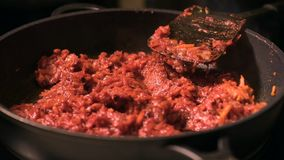Frying vegetables with tomato paste. Chopped onions and carrots fried in vegetable oil with tomato paste in the pan. Close-up on top of a kitchen tile stock footage