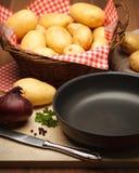 Fryingpan and potatoes Royalty Free Stock Photos