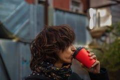 Frysa den unga damen i stilfullt svart lag dricker kaffe arkivfoton