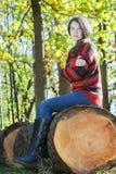 Frysa kvinnasammanträde på den sågade stammen och att krama sig för träd royaltyfri fotografi