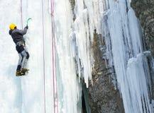 Fryst vattenfall för man klättring Arkivfoton