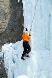 Fryst vattenfall för man klättring Arkivbild