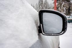 Fryste bils winCars fönster och bils spegel som täckas med snö Arkivfoto