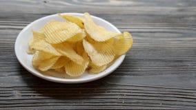 Frytka smażył chips na naczyniu na drewnianym stole, przekąski jedzenia zakąska zbiory
