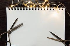 Fryzjerów narzędzia na ciemnym drewnianym tle Pustego papieru notepad z fryzjerów męskich akcesoriów mieszkaniem nieatutowym fotografia stock