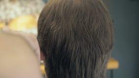 Fryzjer Ciie włosy na świątyni i Nape klient w salonie Mężczyzna obsiadanie w fryzjera karle podczas gdy shearing zbiory