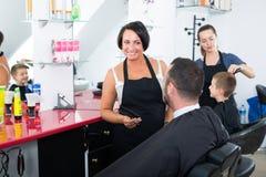 Fryzjer gawędzi męski klient w piękno salonie Zdjęcia Stock
