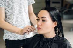 Fryzjer kobiety ` s tnący włosy w salonie, ono uśmiecha się, frontowy widok, zakończenie, portret zdjęcia stock
