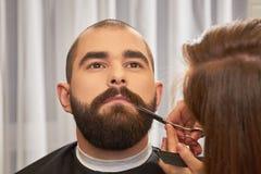 Fryzjer męski żyłuje brodę z nożycami Obrazy Royalty Free